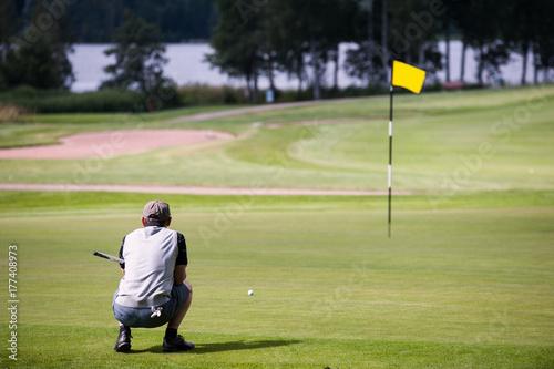 Plakat Mężczyzna planuje następnego uderzenie na golf zieleni żółtej flaga