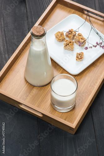 Fototapeta Nabiał. Butelka mleka i szklanka mleka podawana z migdałowymi cukierkami na rustykalnym drewnianym stole.