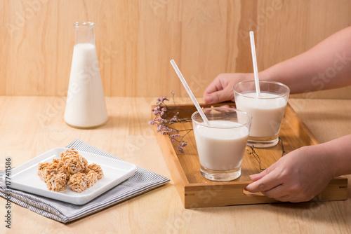 Fototapeta Nabiał. Butelka mleka i szklanka mleka podawać z migdałowymi cukierkami na drewnianym stole.