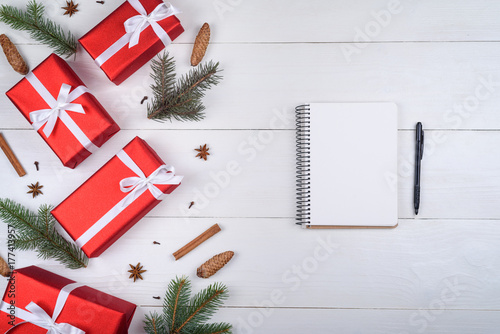 top view of blank notebook on white wooden background with xmas decorations copy space christmas background with notebook for wish list or to do list