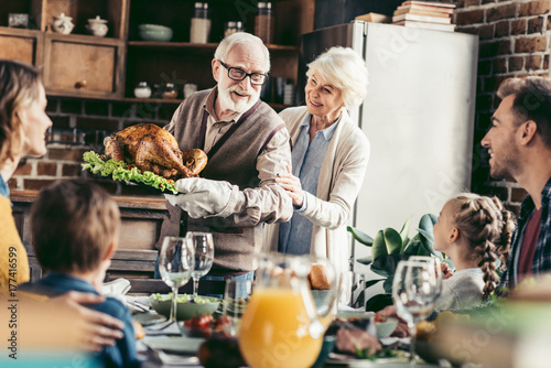 Fotografie, Obraz  grandpa with delicious turkey for thanksgiving