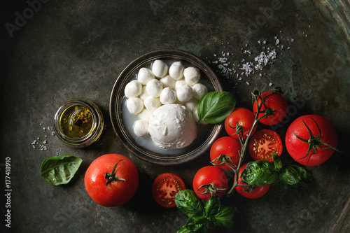 In de dag Buffel Ingredients for italian caprese salad. Mozzarella balls, buffalo in metal vintage plate, tomatoes, basil leaves, olive oil with vinegar over dark background. Top view with space. Rustic style