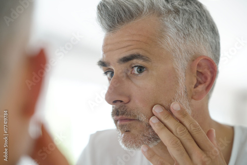 Fotografie, Obraz  Middle-aged man applying cosmetic on his face, mirror view