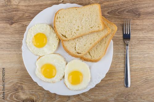Zdjęcie XXL Smażone jajka, kawałki chleba w biały danie i widelec