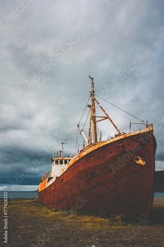 Foto op Canvas Schipbreuk A rusty ship wreck stranded at a beach