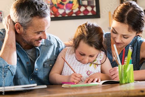 Valokuva  Mom and Dad help their little girl do homework for school