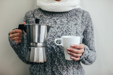 Woman With Chunky Knit Sweater Holding A Hot Cup Of Coffee And Coffee Pot. .