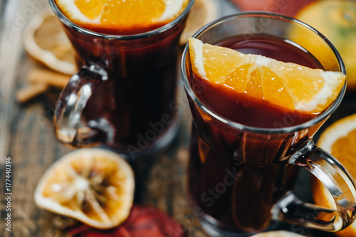 Closeup Hot mulled wine with dry orange slices, cinnamon sticks on wooden board. Christmas or winter warming drink with recipe ingredients around.