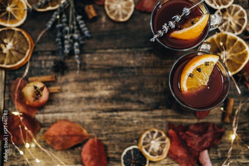 Hot mulled wine with dry orange slices, lavender and cinnamon sticks on wooden board. Christmas or winter warming drink with recipe ingredients around. Top View