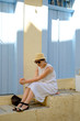Young beautiful girl in a straw hat, sunglasses, a white dress sitting on stairs