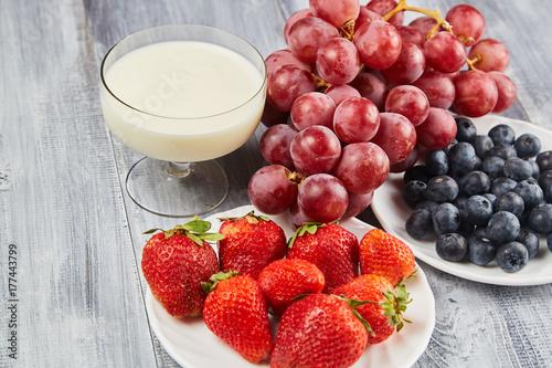Plakat Truskawka, czarna jagoda z jogurtem i winogrona na szarym drewnianym tle
