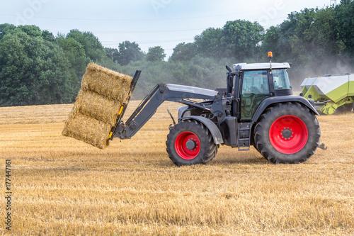 Photo  Schwarzer Traktor transportiert Strohballen, Seitenansicht