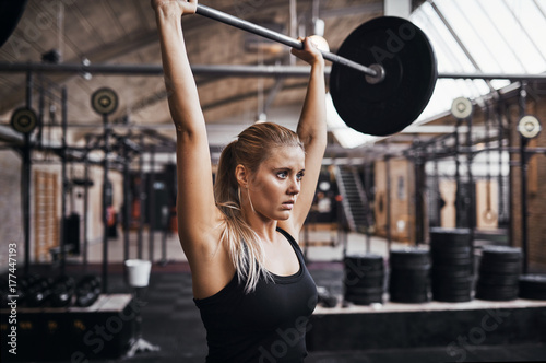 Fényképezés  Young woman lifting barbells over her head in a gym