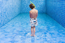 Boy Stands In An Empty Blue Sw...