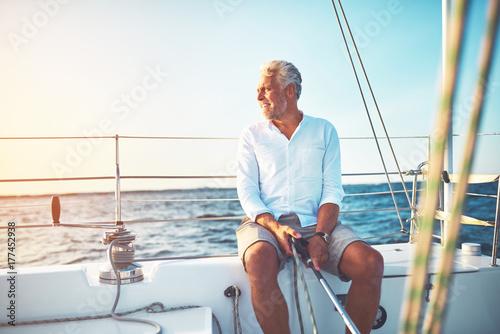 Fotografia  Mature man sailing his boat on the open ocean