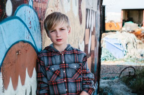 A pre-teen boy standing in front of a graffitied container.
