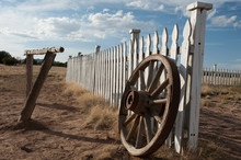White Wooden Picket Fence With Wagon Wheel Resting Against The Fence In A Rural Setting.