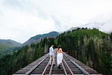 A Young Beautiful Couple Walking Across A High Bridge