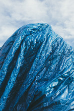 Blue Tarpaulin Covering Pile O...