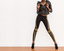 Fashion Model In A Black Top And Black Tights With Gold Trim