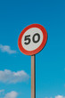 Round Speed Limit Road Sign Above Blue Sky