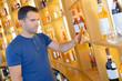 Man choosing bottle from shelf in store