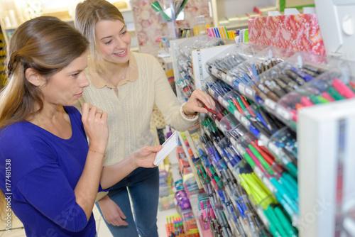 Plakat dwie kobiety wybierają przybory szkolne w supermarkecie