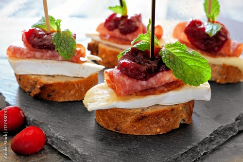 Tuinposter Voorgerecht Holiday crostini appetizers with cranberry sauce, brie, salami, and mint close up on a slate server