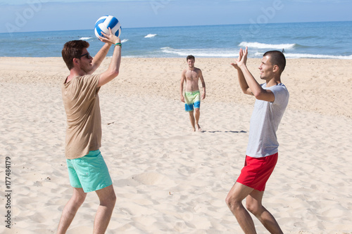 Plakat grupa młodych radosnych dziewcząt gry w siatkówkę na plaży