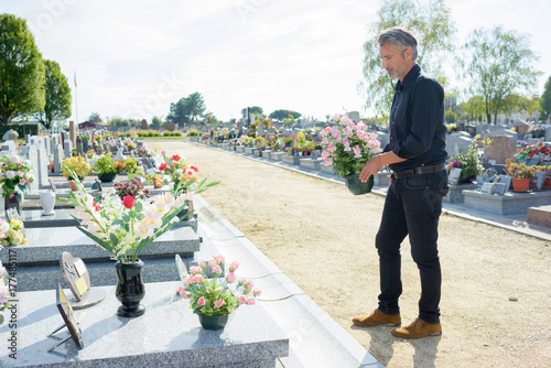 Foto op Canvas Begraafplaats Man by graveside holding pot of flowers