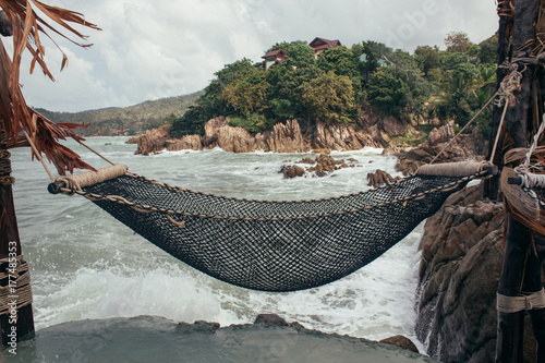 A net hammock on a cliff being splashed by the oceans waves