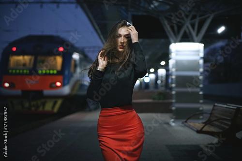 Plakat Piękny młody eleganckiej kobiety podróżnika czekanie dla pociągu przy wieczór dworcem