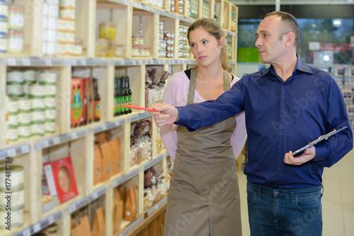 Fototapeta Kierownik sklepu kontrolujący wyświetlacz z pracownikiem