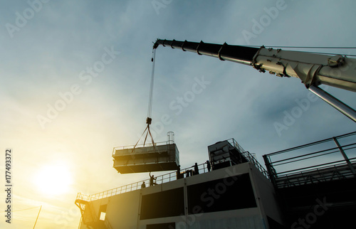 Fotografie, Obraz  mobile crane lifting Cooling machine, silhouettes at sunset