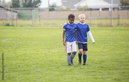 Fotografie, Obraz  Two soccer teammates walking off the field after a loss