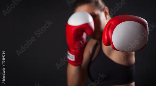 Obraz na płótnie Żeński bokser z czerwonymi bokserskimi rękawiczkami, czarny tło z kopii przestrzenią