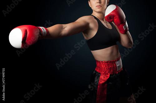 Plakat dziewczyna uderza w czerwone rękawice bokserskie, kobieta bokser na czarnym tle