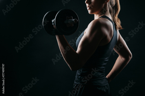 Fototapeta girl exercising squatting with dumbbell on black background with copy space obraz