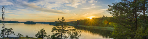 Fototapeta Panorama picture taken in Sweden with sunset over a lake and beautiful glow from the sun obraz