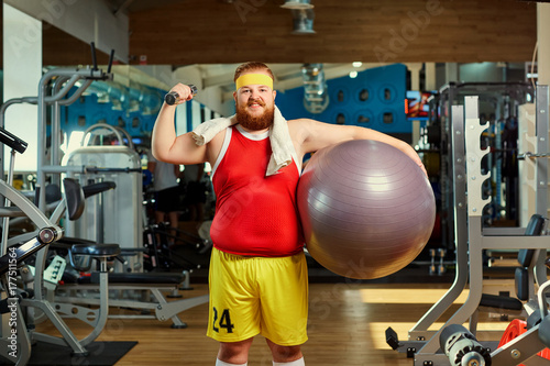 Plakat Gruby śmieszny mężczyzna z dumbbells i piłkami w gym.