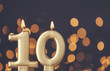 canvas print picture - Gold number 10 celebration candle against blurred light background