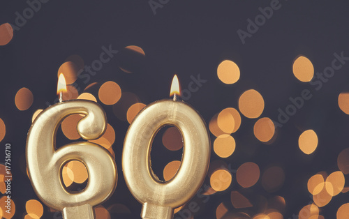 Fotografia  Gold number 60 celebration candle against blurred light background