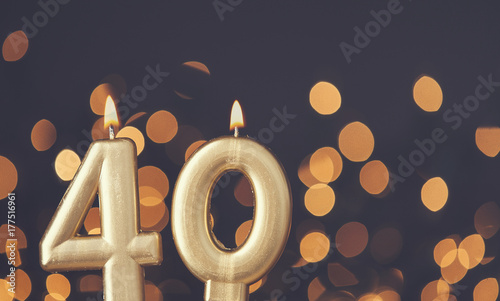 Fotografia  Gold number 40 celebration candle against blurred light background