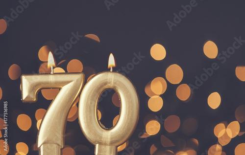 Fotografie, Obraz  Gold number 70 celebration candle against blurred light background