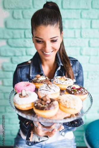 Beautiful young woman enjoying in delicious glazed and decorated donuts. Selectiv focus.