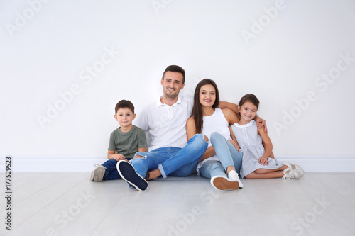 Fotografie, Obraz  Happy family sitting on floor at new home