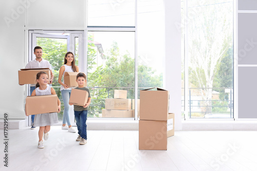 Fotografie, Obraz  Happy family with moving boxes entering new house