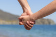Couple hands held together on a natural sea background