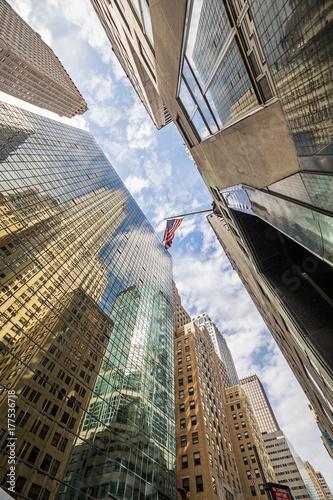 wysokie-budynki-na-manhattanie-widocznie-z-dolu-z-flaga-usa-na-samej-gorze