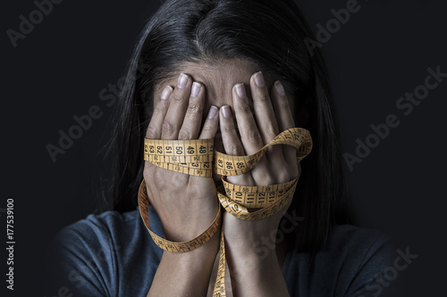 Photo hands wrapped in tailor measure tape covering face of young depressed and worrie